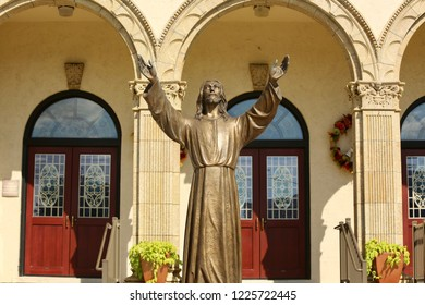 Exterior of church with statue of Jesus.