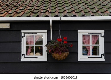 The exterior of the classic dutch style house is covered with black wood, white windows are hanging from the middle of the flowerpot