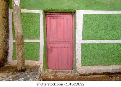 Exterior of colourful house with green plasterwork and pink metal door in Harar, Ethiopia.
