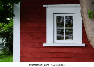 The exterior corner wall of a red house with white trim. A window with four panes of glass is framed in thick white wood. The exterior wall is narrow red clapboard. There are trees in the background.