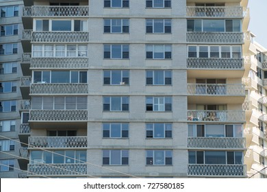 Exterior day time establishing photo of a generic tall apartment building with balcony facade