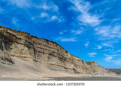 Exterior daytime stock photo of grassy cliff in foreground against blue semi cloudy sky background at Drakes Beach in Point Reyes National Seashore, Point Reyes Station, California in the summer