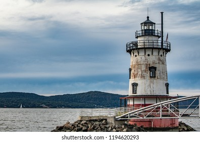 Exterior daytime stock photo of metal bridge leading to Sleepy Hollow Lighthouse in Sleepy Hollow, New York in foreground and Nyack across the Hudson River in background on semi cloudy day