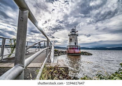 Exterior daytime wide angle stock photo of metal bridge leading to Sleepy Hollow Lighthouse in Sleepy Hollow, New York in foreground and Nyack across the Hudson River in background on semi cloudy day