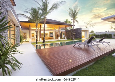 Exterior design of spacious modern luxury pool villa. Feature wooden decking, sunbed, big swimming pool and greenery garden