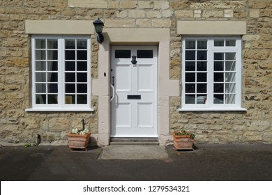Exterior Detail of a Beautiful Old English Stone Cottage House with a White Wooden Front Door and Wood Framed Windows