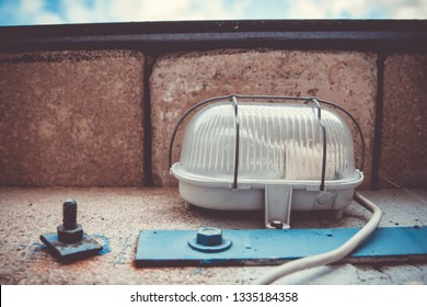 Exterior electric light fitting on bricks with plastic cover protected by wire frame and cord leading towards the camera