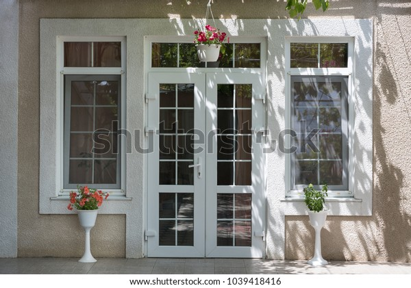 Exterior - entrance to the house, Flowers in pots, shadow from grapes cover above