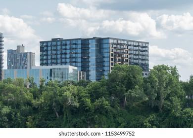 Exterior establishing shot of luxury apartment building real estate along beautiful promenande treeline on outskirts of urban city.