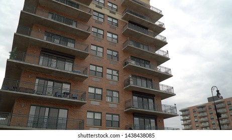 Exterior establishing shot view of a luxury apartment building along the coastal shore. Sliding glass doors lead out to balcony on brick construction facade