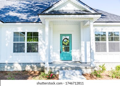 Exterior facade of a white new construction house with a vibrant turquoise front door
