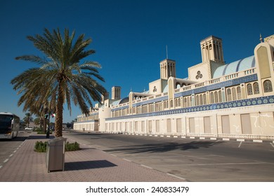 Exterior of the Famous market of Sharjah, United Arab Emirates. Palm trees in front of the building. Empty parking lot.