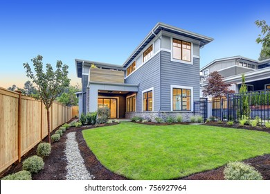 Exterior of grey blue craftsman style home with Welcoming backyard and covered patio. Northwest, USA