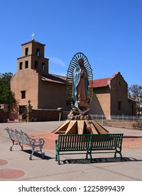 the exterior of the historic church of our lady of guadalupe,  bench,  and courtyard  in santa fe, new mexico