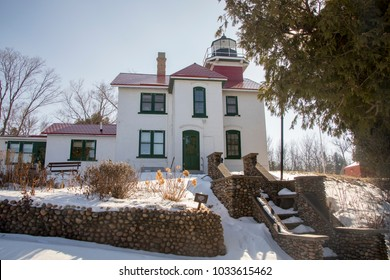 Exterior of historic Grand Traverse Lighthouse in Traverse City on Traverse Bay, Michigan along shores of frozen Lake Michigan in winter.
