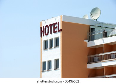 Exterior of a hotel against clear blue sky with satellite dishes