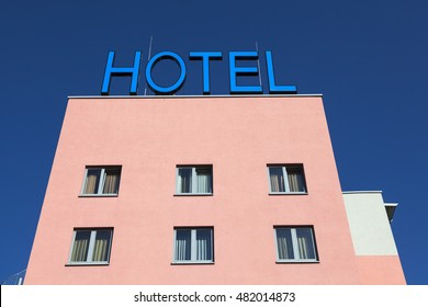 Exterior of a hotel building with a blue Hotel sign on top