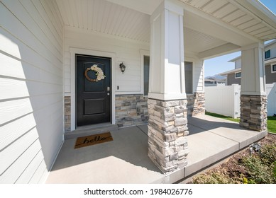 Exterior of a house with black wooden door with flower wreath, white walls and bricks. Front door entrance with window, posts with bricks and a concrete floor, there is a lawn and fence at the side.