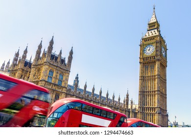 Exterior of House of Parliament in London with red buses passing by in motion