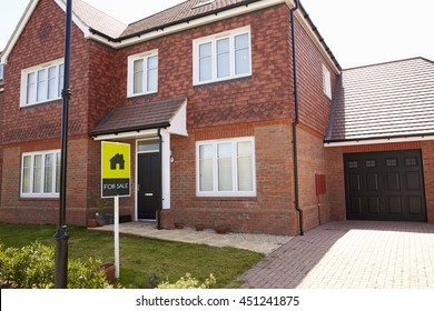 Exterior Of House With Sold Sign In Garden