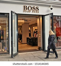 Exterior of Hugo BOSS luxury store in Oslo. The fashion brand has made the history of elegance for men and women. People walk along the street. Shopping in Norway. Oslo – November 4, 2017