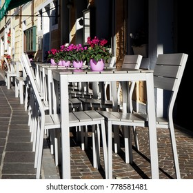 Exterior of an italian bar on the street with white chairs and tables. In every table there is a cyclamen pot