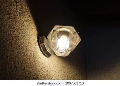Exterior lamp on wall by night. Old fashioned black metal and glass lamp. Tungsten bulb.