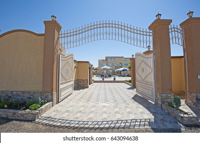Exterior of large metal gated arched entrance to luxury summer holiday tropical villa resort with blue sky