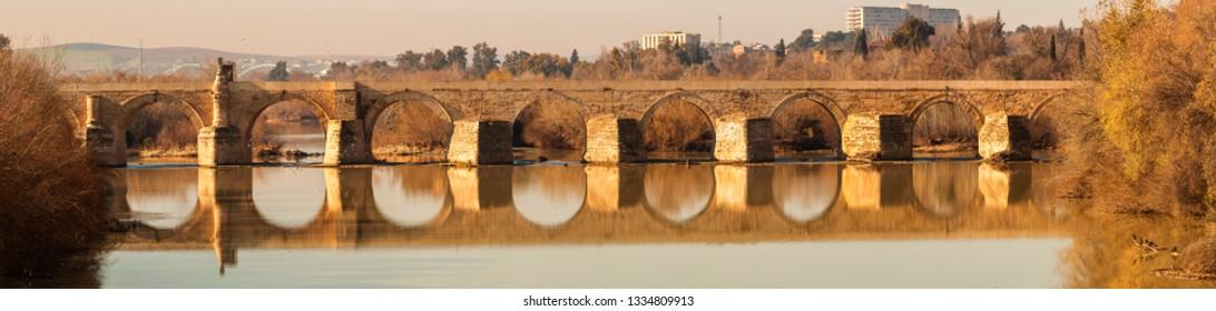 Exterior of long stone Roman bridge crossing Guadalquivir river with tranquil water in autumnal sunlight in Cordoba, Spain