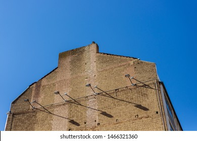 Exterior low angel of elevated old rough refractory naked brick wall facade with hanging lamp and its shadow at the side of apartment building against deep blue sky. Typical character brick building.