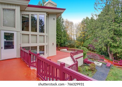 Exterior of a luxury home. Empty red multi level wraparound deck with breathtaking view.