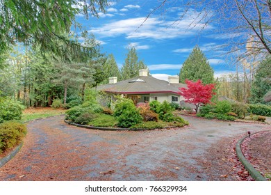 Exterior of a luxury home. View of the circular driveway, entrance porch and inviting autumn front yard