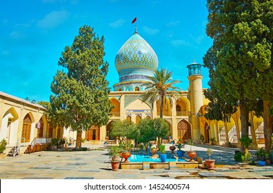 Exterior of medieval Ali Ibn Hamzeh Holy Shrine, decorated with arched niches, carved wooden Persian screens, scenic bulbous dome with rich tile patterns and small garden, Shiraz, Iran