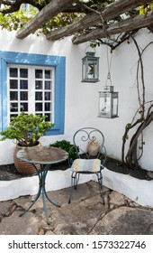 exterior mediterranean traditional architecture, lanzarote spain. Romantic vintage seating area. Garden terrace with blue weathered iron chair and table. White wall and blue window. travel background.