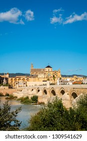 Exterior of Mezquita (mosque- cathedral) with fence and lush green trees on shore of Guadalquivir river in Cordoba, Spain