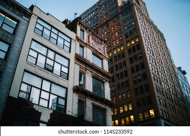 Exterior of modern constructed real estate with lights in office windows located in downtown, tall buildings with rental apartments for residents and commercial property for corporation and companies