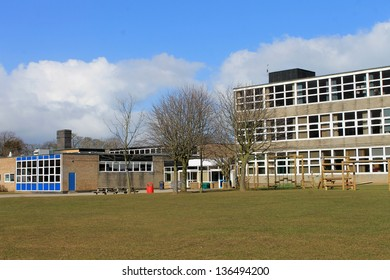 Exterior of modern school building with playing field in foreground.