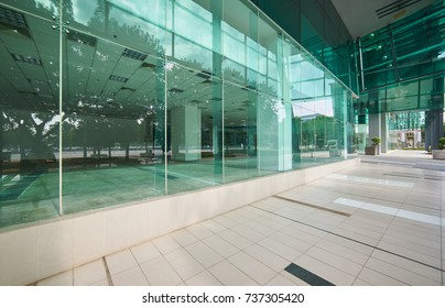 Exterior of a modern steel  and green glass office building with empty walkway. panoramic and perspective view. Abstract ,inspirational ,artistic and modern architect design .