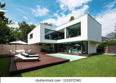 Moderna villa blanca exterior con piscina y jardín, nadie dentro
