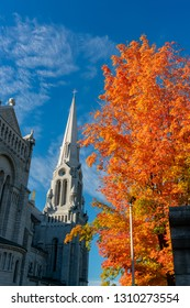 Exterior morning view of the Basilica of Sainte-Anne-de-Beaupre church with red maple tree at Quebec, Canada