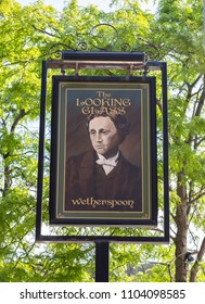 An exterior mounted pub sign for the pub The Looking Glass in Warrington Cheshire May 2018