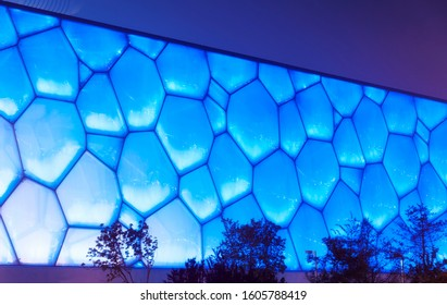 The exterior of the National aquatic center in Olympic park in Beijing China lit up at night blue.