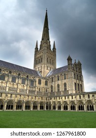 Exterior of Norwich Cathedral and tower under cloudy sky, Norwich, England, UK