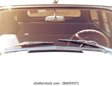 Exterior of the old automobile with windshield wipers, steering wheel and front window. Retro car in vintage toned effect with copy-space for text. Oldtimer automobile, front view.