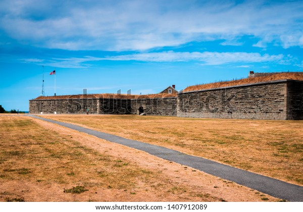 Exterior of Old Revolutionary War Fort Ontario in Oswego, NY with blue cloudy sky and brown dead grass.