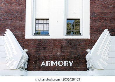 Exterior of old vintage armory building with art deco white eagles on a brick building.