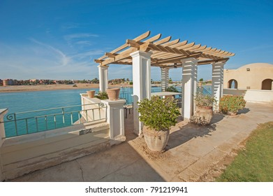 Exterior outdoor dining area under pagoda at a luxury tropical holiday villa with marble table and waterfront river view