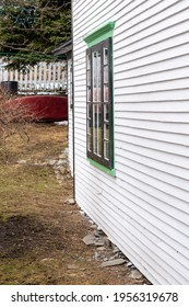 The exterior outside wall of a stark white heritage wood building with vibrant green trim. The country style house has narrow clapboard and a single double hung window with lace curtains hanging.