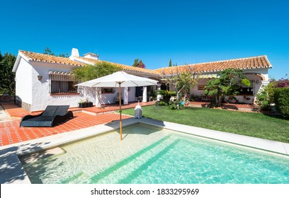 Exterior panorama of a relaxing holiday villa with a swimming pool with tanning ledge,chair pool,umbrella, grass,garden, porch and gazebo.