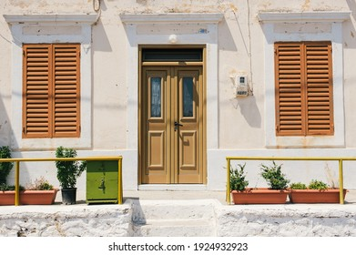 a exterior part of the home with wooden door white wall windows of home nearby green plant pots in the village